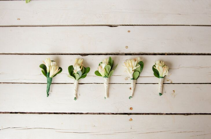 The boutonnieres were made up of ivory tuberoses and greenery wrapped in ivory ribbon.