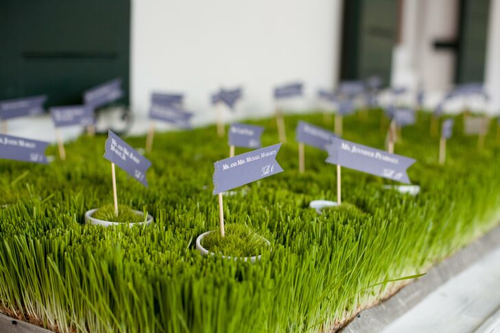 Miniature double-pennant escort cards in tiny pots of moss were displayed in bright green grass.