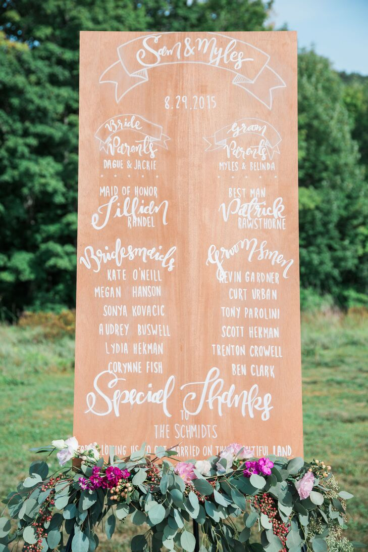 Adorned with whimsical white calligraphy and a eucalyptus garland dotted with vibrant purple blooms, Samantha and Myles's welcome sign set a playful, romantic tone for the alfresco ceremony.