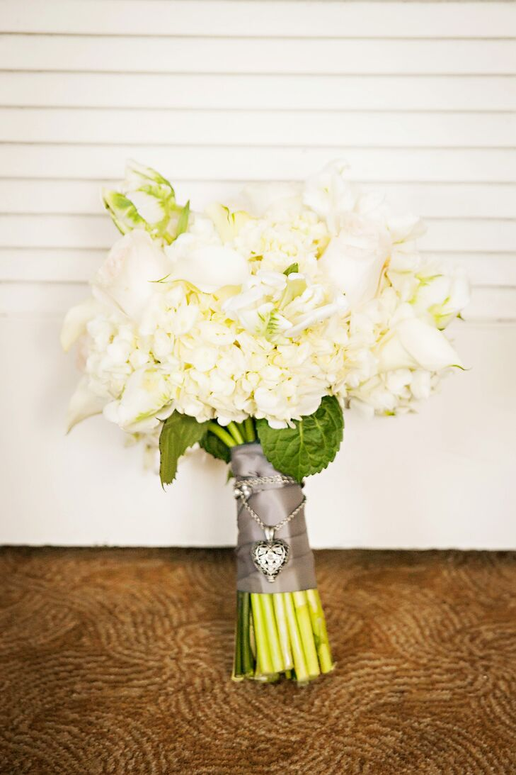 Complementing the light pink venue, Kelly walked down the aisle with a bouquet of white calla lilies and hydrangeas tied with a gray ribbon and crafted by Two Birds Events. A locket filled with the ashes of Kelly's brother were also tied around the bouquet to honor his memory.