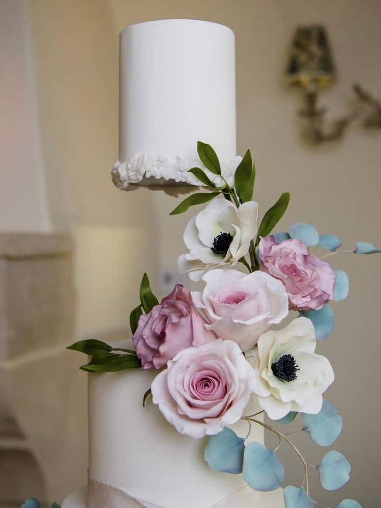 Close-up of floating top wedding cake tier with spacer hidden by flowers