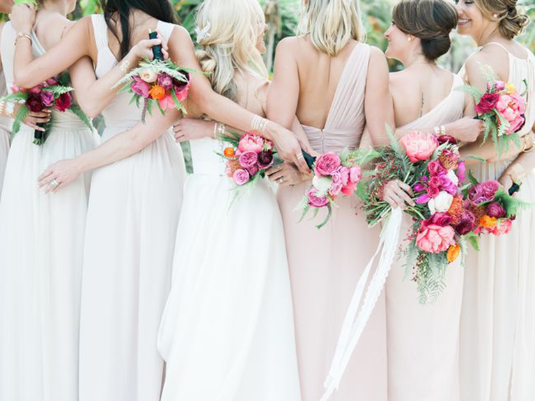 Bridesmaids standing with arms around each other