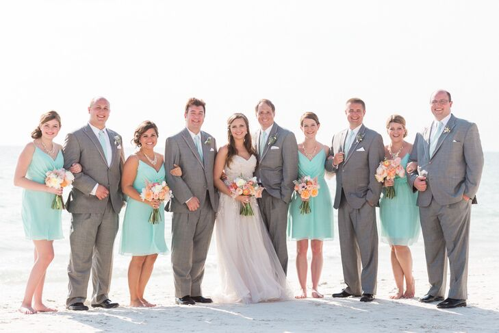 Her bridesmaids were ready for the beach (and Florida's heat) in short mint Jim Hjelm dresses. Each had a chiffon skirt that flowed from the empire waist and ruching along its bodice. The women paired their looks with the same gold necklaces and updo hairstyles. To match them, the groomsmen wore gray suits from Men's Wearhouse with mint ties.