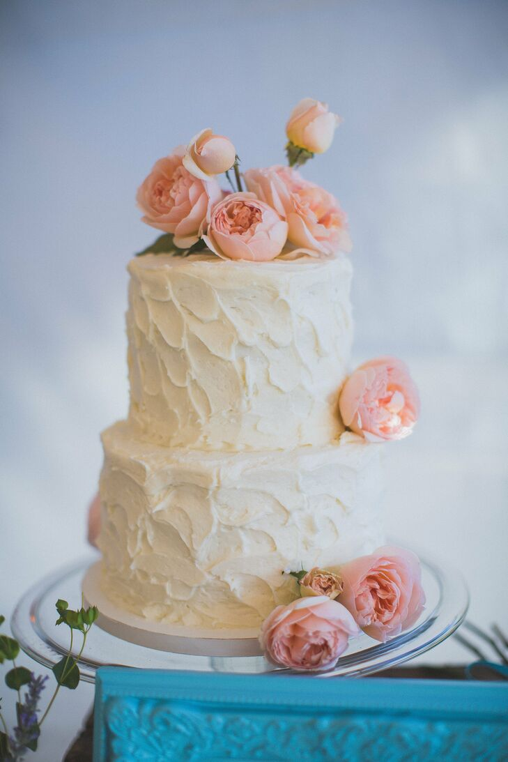 The simple two-tired buttercream cake was topped with a bunch of fresh, pink peonies and had a spooned frosting pattern for a homemade look.