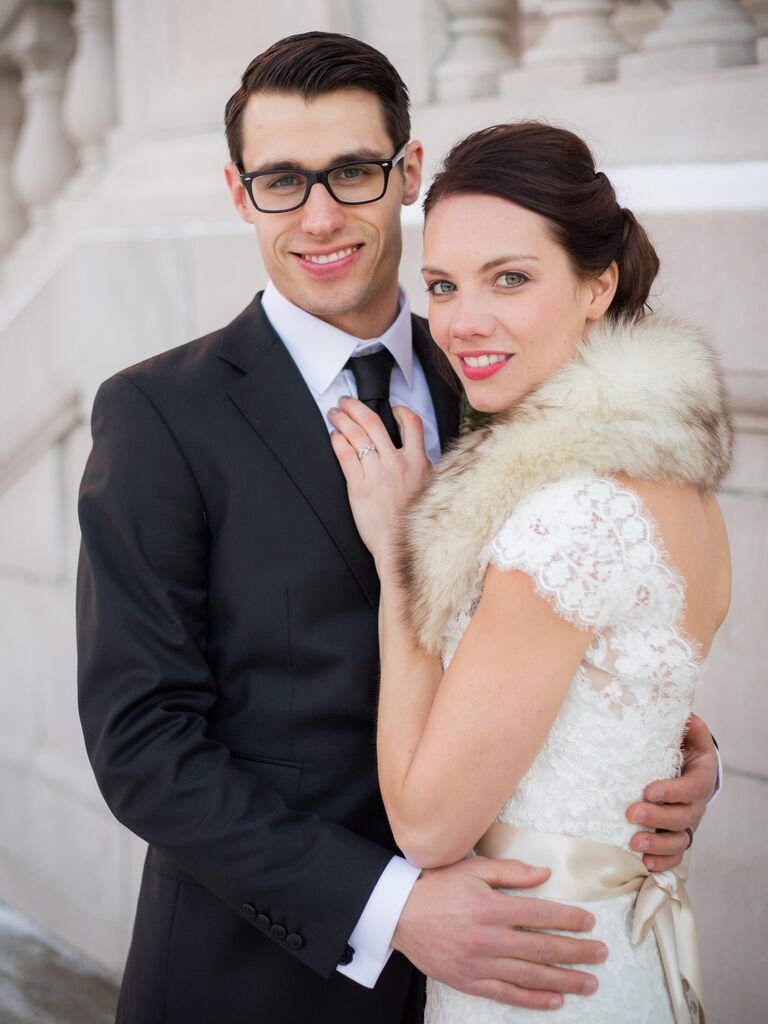 Groom in a black suit and black tux with his bride in a lace dress and fur stole