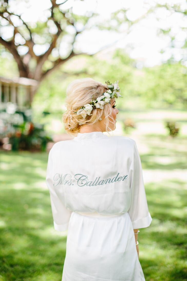 "During prep for the wedding day, Olivia wore a custom silk robe sewn with ""Mrs. Callander""—her married name—on the back in teal thread."