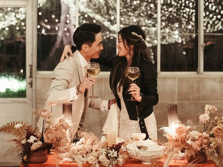 Groom with bride wearing leather jacket toasting during wedding reception