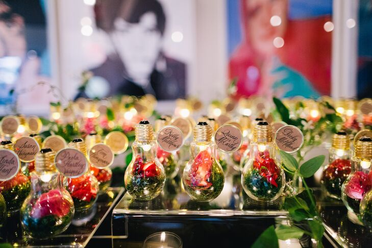 Playing off the evening's garden theme, the couple handcrafted one-of-a-kind escort cards with undeniable whimsical flair. Lightbulbs filled with battery-operated LEDs, moss and pink calla lilies were trimmed with hand-calligraphed cards that guided guests to their seats.