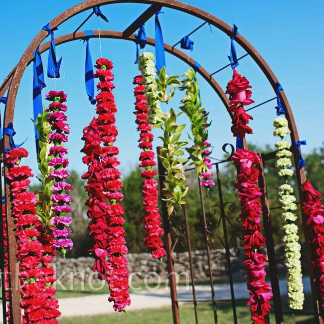 Colorful floral garlands hung from a metal arbor.