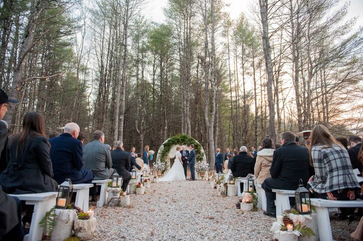 """The day unfolded with a quaint outdoor ceremony at sunset in quaint clearing on the Flanagan Farm property. """"We are lovers of the outdoors, so this setting seemed perfect,"""" Jill says. White benches lined the aisle, with birch logs bearing lace doilies, candlelit lanterns and moss giving the decor a touch of woodland romance. """"To brave the weather, we had blankets in different materials and shades of ivory available in baskets for our guests. We also provided a table with programs and hot apple cider,"""" Jill says."""