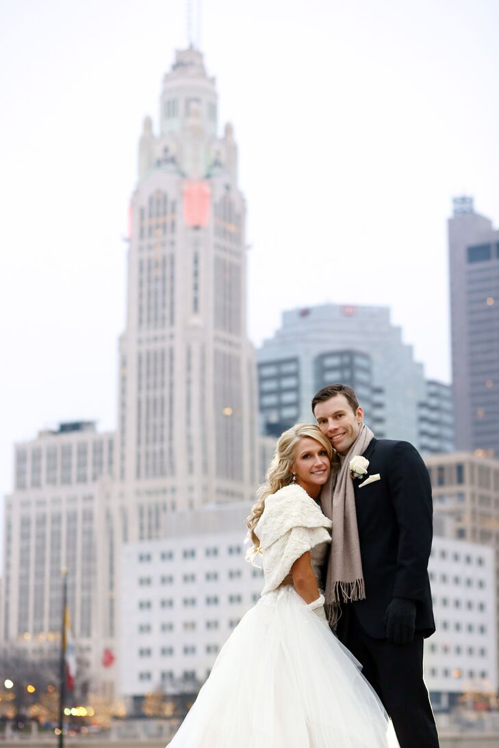 Lisa and Mark posed for a picture with an urban backdrop of Columbus, Ohio. The couple put on a few pieces of winter clothing after the ceremony finished. Lisa wore an ivory fur stole over her wedding dress, while Mark wrapped a brown scarf around his neck.