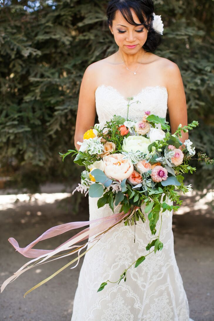 Naomi held a soft-colored bouquet filled with garden roses, peonies, roses and smaller floral accents mixed with hanging greenery. The flower arrangement was tied around the stems by dangling pieces of pink ribbon.