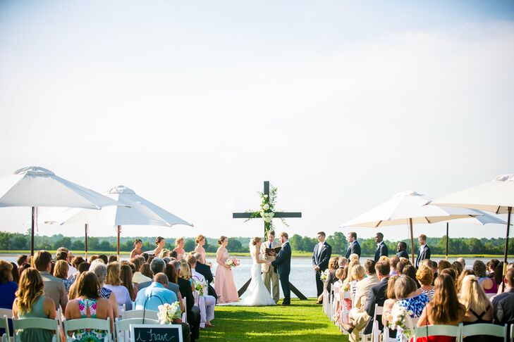 As Haley and Dillard exchanged vows in front of the breathtaking view of the water, a 12-foot cross stood behind them covered in greenery and hydrangeas. Guests sat in rows of white chairs facing the water under scattered white umbrellas.