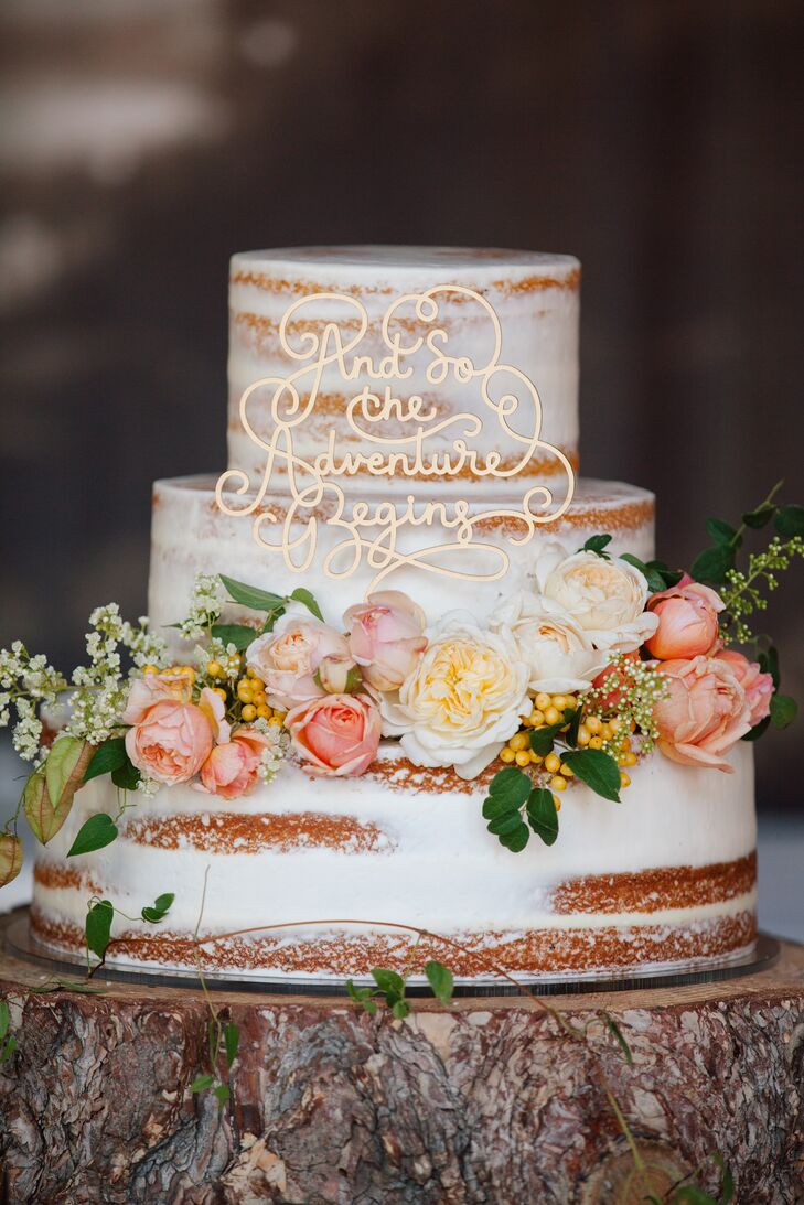 "The rough-frosted wedding cake by Granite Bakery and Bridal Showcase was decorated with fresh, blush pink rosebuds. A golden cake topper read: ""And so the adventure begins."""