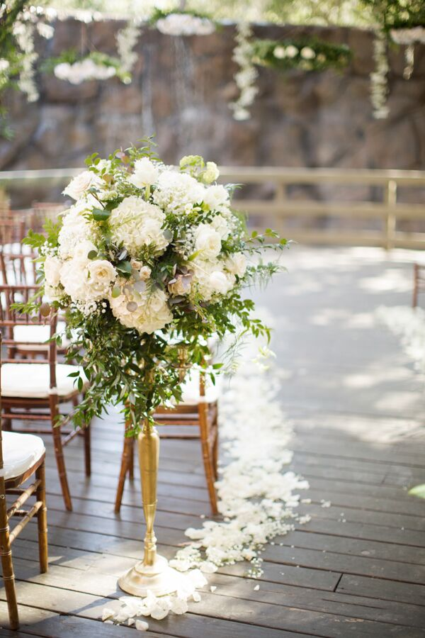Blossoming white peonies and roses were placed on slender brass holders along the aisle at the outdoor garden ceremony.