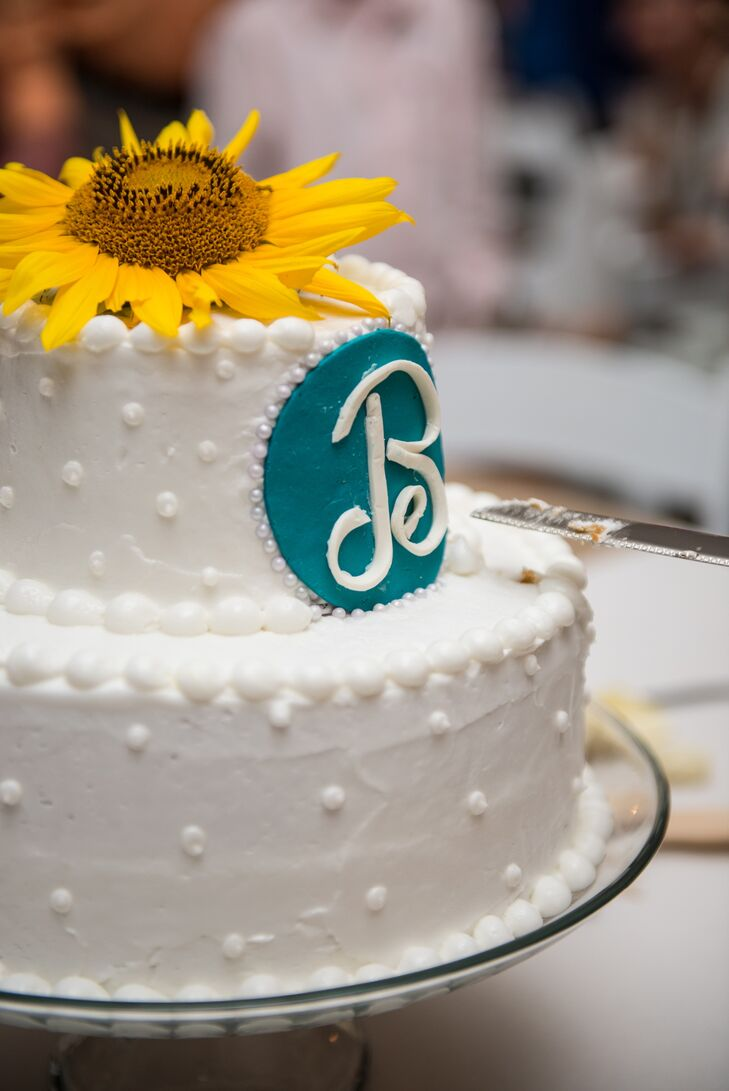 "A fresh sunflower topped the simple two-tiered buttercream cake with swiss dots and pearl piping. ""A retired family friend graciously made our cake because she knows, no one can make cake like hers!"" says Kasi."