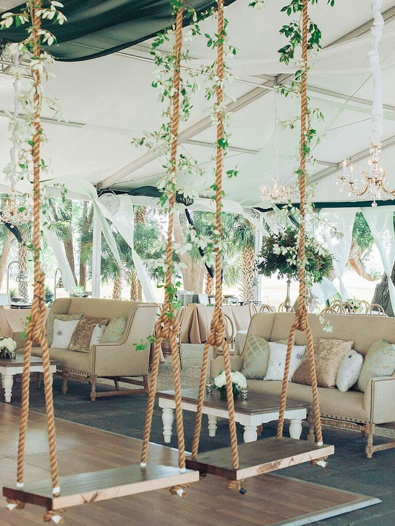 Whimsical rope swings with green vines in wedding tent