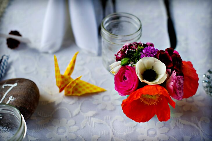 Alexandria handmade the colorful origami cranes that decorated the long reception tables in the barn. Simple, small and bright flower arrangements with flowers sourced from Bathtub Farms, a local organic farm, added a pop of color to the white, floral-pattered table linens.