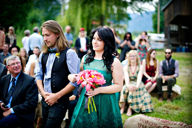 The couple had no color palette, and encouraged the wedding party and guests to dress casual and however they wanted. This bridesmaid's green fit-and-flare dress complemented the outdoor, rustic ceremony perfectly. A bouquet of pink flowers added a soft, romantic touch to her look.