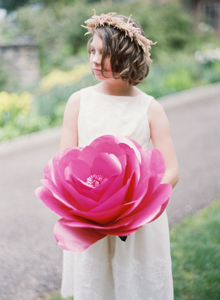 """Even though we chose a more natural setting for the ceremony, it was still magical and enchanting with the added flowers,"" Nicole says. A giant oversize paper flower, carried by the flower girl, really gave the ceremony an ""Alice's Adventures in Wonderland"" feel."