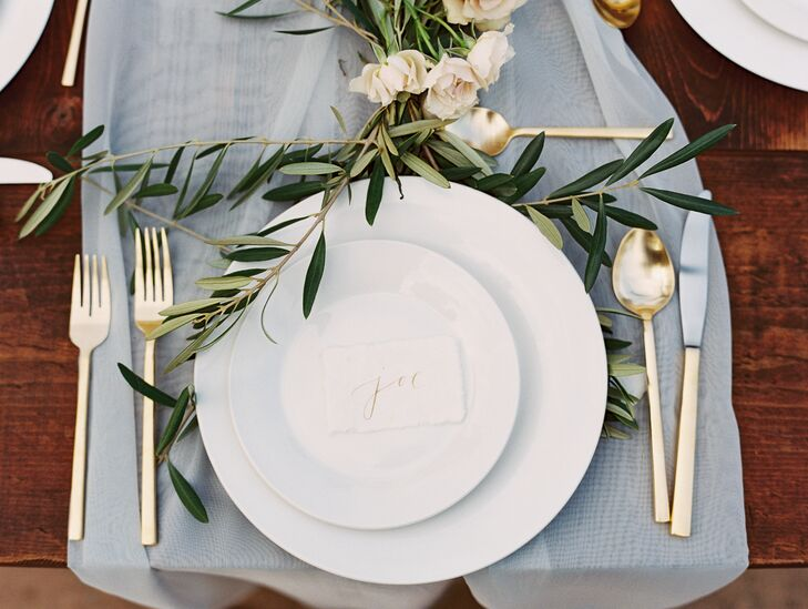 Nicky found white plates trimmed with gold on Etsy and paired them with glasses etched with gold. Gold silverware rested on the sides of the display, and a white escort card with gold calligraphy labeled each seat.