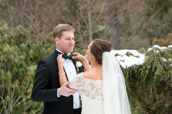 Edward wore a traditional black tuxedo from the Black Tux for his timeless winter wedding. He completed his look with a David Donahue silk Black Watch tartan bow tie. The pattern was inspired by Emily's Scottish heritage and the six months she lived there in college.