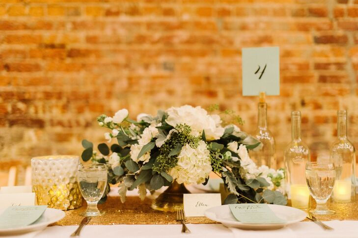 Passionflower of Ann Arbor, Michigan, created lush green and white arrangements on gold pedestal vases using a mix of eucalyptus, hydrangeas and ranunculus.