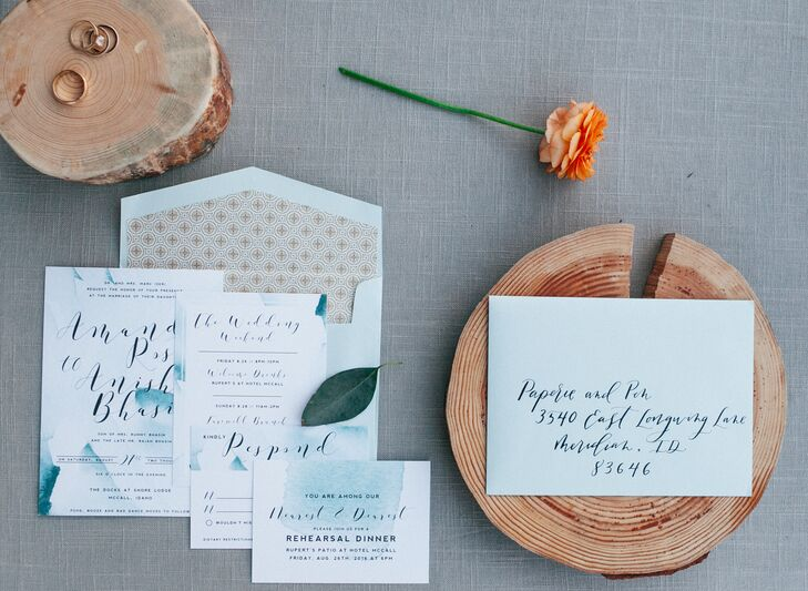 "Paperie + Pen created the blue-and-green-hued invitation suite. ""The invitations were a watercolor design in blues and greens. The invitations really inspired a lot of the wedding's design,"" says Amanda. ""The sea-glass place cards, with each guest name in gold calligraphy, were one of our favorite elements, and guests took them home as mementos."""