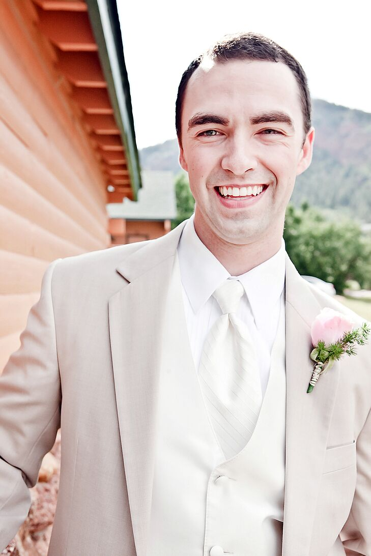 The groom wore a tan and white suit with a white vest and tie. He completed his look with a blush rose boutonniere.