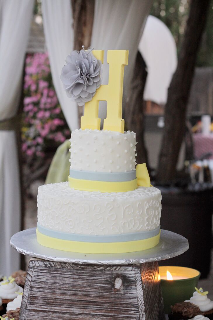 Nicole and Derrick enjoyed a two-tier white wedding cake decorated with gray and yellow fondant from The Sweet Spot Bakery.