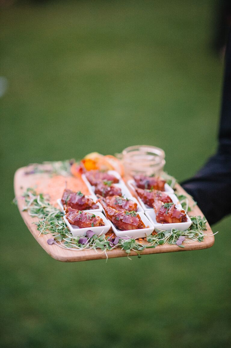 Server holding bacon wrapped quail bites