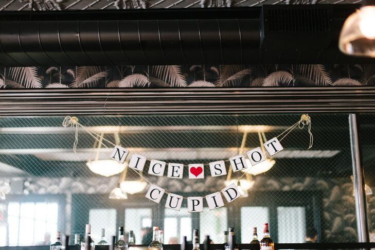 "Valentine's Day-themed details included heart-shaped confetti, arrow coasters and a paper banner that read ""Nice Shot Cupid""—a cute touch that the couple found on Etsy.com"
