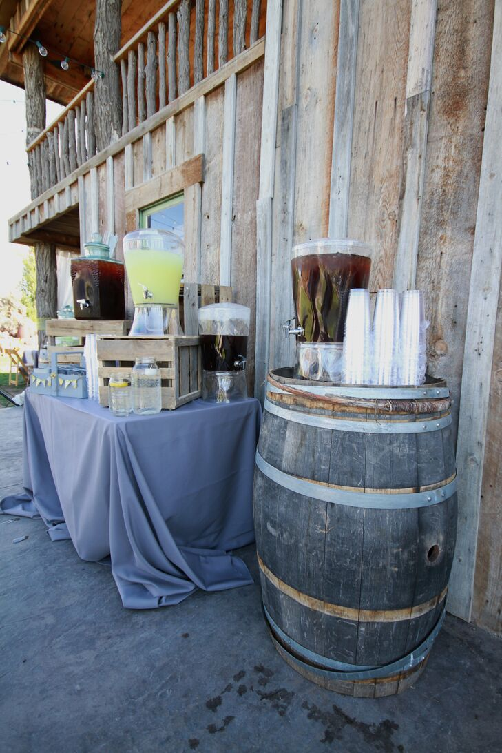 The iced tea and lemonade drinks were displayed on rustic wood barrels and crates to match the country wedding theme.