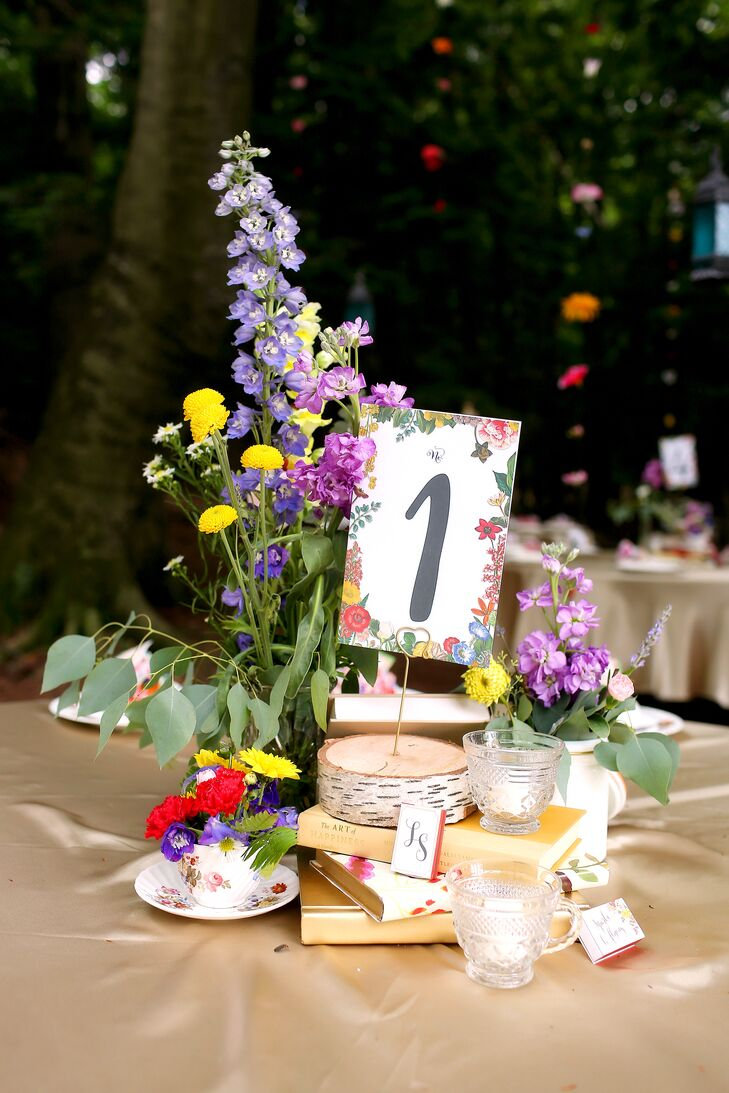 Reflecting the setting, the centerpieces had a whimsical, woodland appeal. Vintage books spray-painted gold or wrapped in floral paper served as the base of the arrangements and were topped with bud vases and tea cups filled with brightly hued wildflowers, citronella candles displayed in vintage glass cups and birch accents.