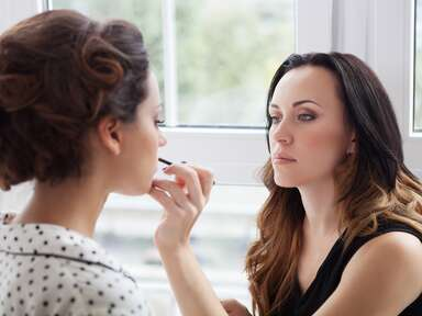 woman getting professional makeup done by makeup artist