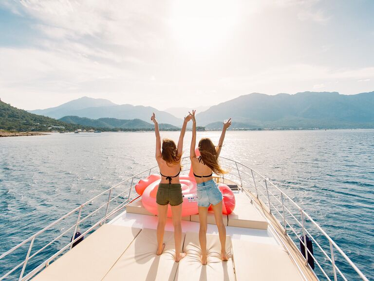 two girls in bikinis and shorts on the front of a boat on a lake