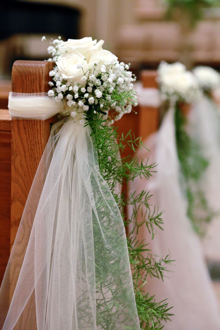 The wooden pews on the ceremony aisle was decorated with ivory roses, baby's breath, green garlands and sheer sashes for Molly and Andrew's wedding.