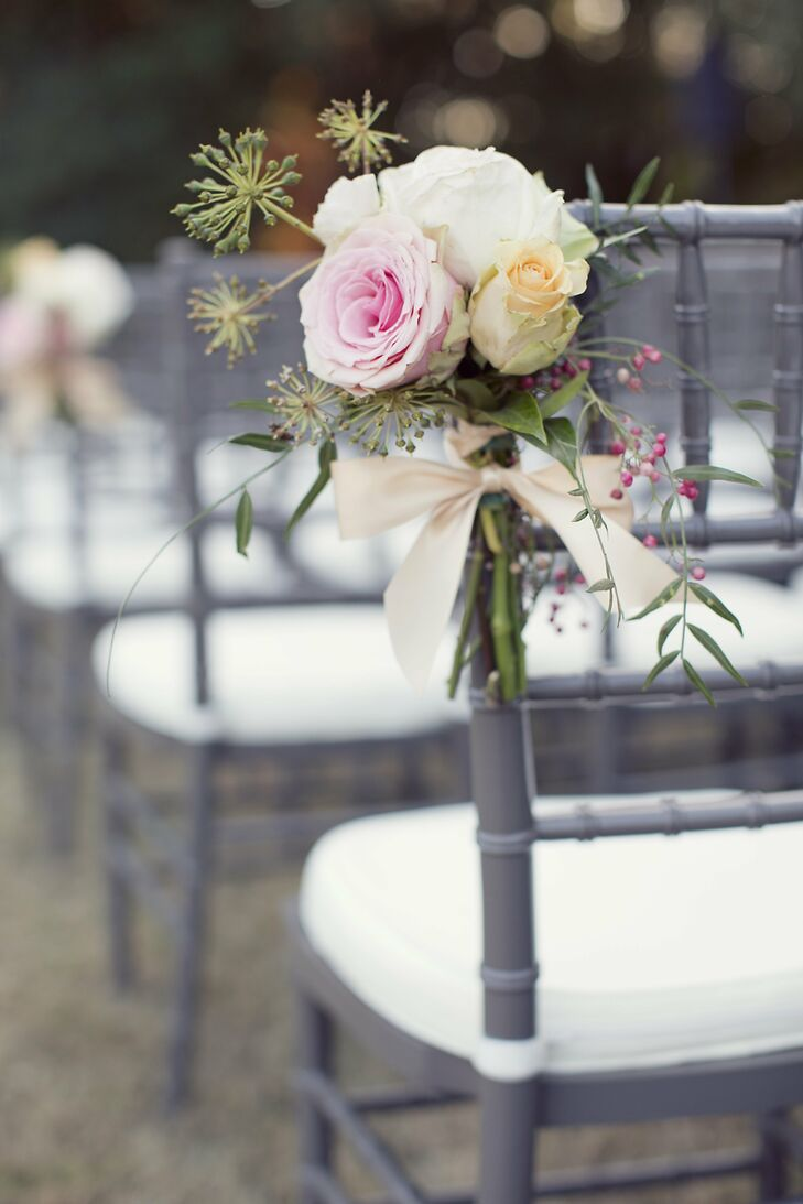 Small bunches of pastel roses were tied to the gray ceremony chairs.
