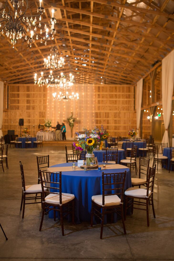 Royal blue linens added a bright pop of color in the rustic cedarwood barn reception. Burlap table runners and neutral chiavari chairs tied the rustic theme together.