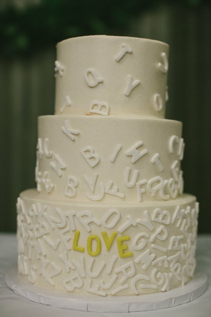 """The buttercream cake was topped with white cascading alphabet letters; yellow ones spelled out """"love."""""""