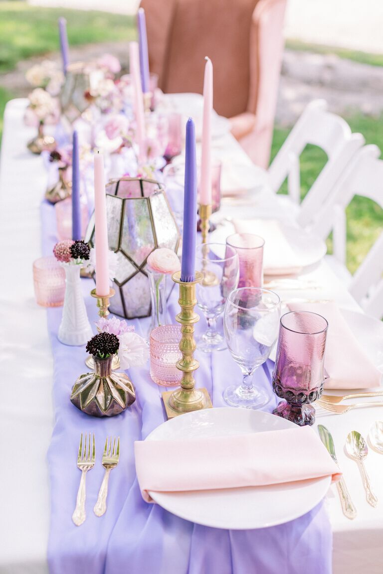 outdoor reception tablescape showcasing 2021 wedding colors light purple pink tall candles gold brass accents