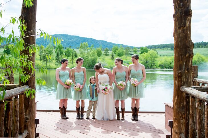 Meghan stood in the middle of her bridesmaids and next to her ring bearer. Her bridesmaids wore knee-length mint green dresses paired with dark brown cowboy boots.