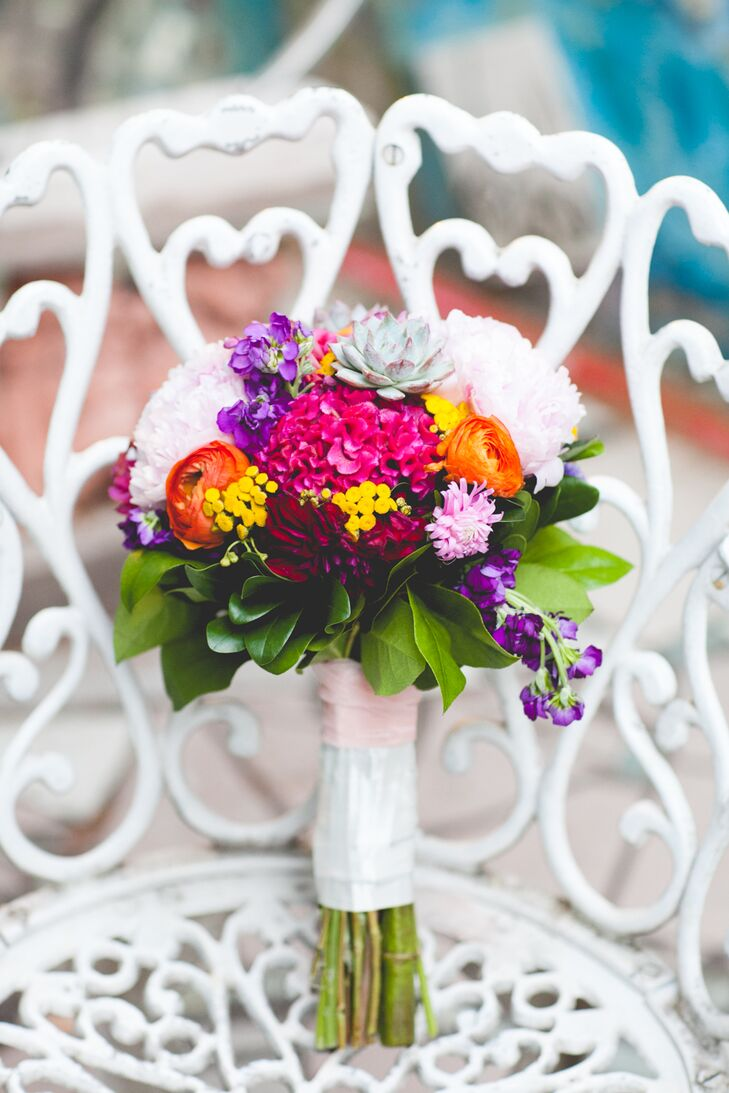 Robin held a bouquet of orange garden roses, magenta hydrangeas, white peonies and a variety of small colorful flowers that were mixed with succulents and green accents.