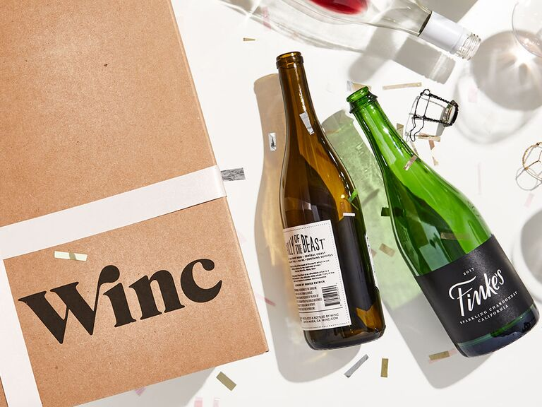 Brown package with Winc in black lettering next to empty wine bottles