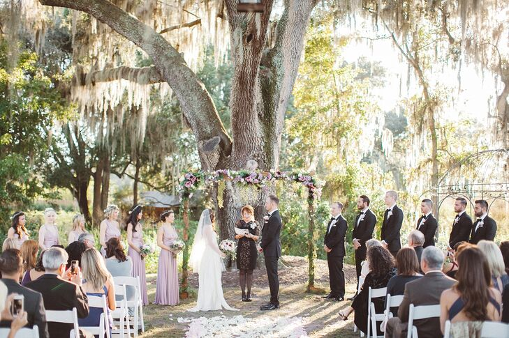 Nikole's aunt played a very specific role in the ceremony. She was their officiant. They were married in front of a romantic floral wedding arch decorated with shades of burgundy, blush, white and pink.