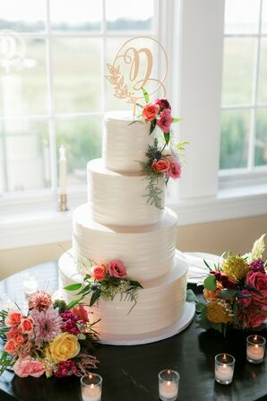 Elegant Tiered Wedding Cake with Topper and Colorful Flowers