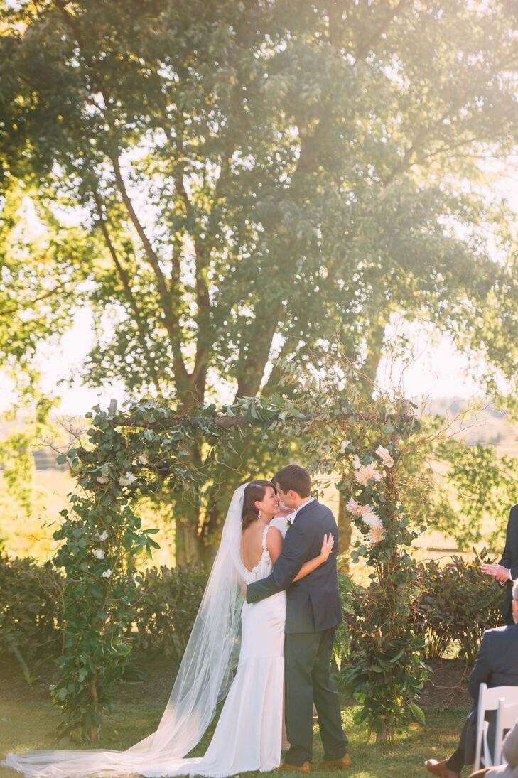 Molly and Ryan were married under a wooden wedding arbor that was decorated with greens and ivory dinner plate dahlias.