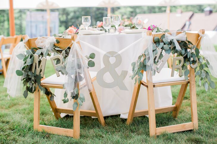 "Samantha and Myles savored a few private moments during their reception at their sweetheart table. To set the spot apart from the rest, the couple adorned their chairs with panels of airy white tulle, silver ""Mr."" and ""Mrs."" signs and lush eucalyptus garlands."