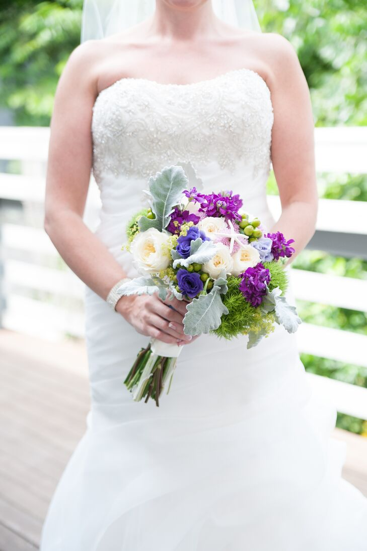 Melanie wore a strapless, trumpet-style gown with an embellished bodice on her wedding day. She carried a bouquet with ivory peonies, indigo roses, purple stock, dusty miller, hypericum and greens on her wedding day.