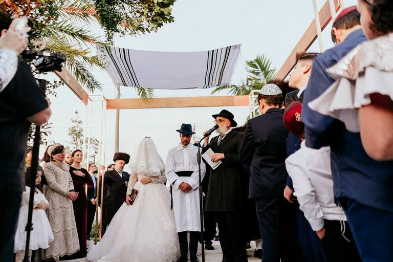 Couple under chuppah at Orthodox Jewish wedding ceremony